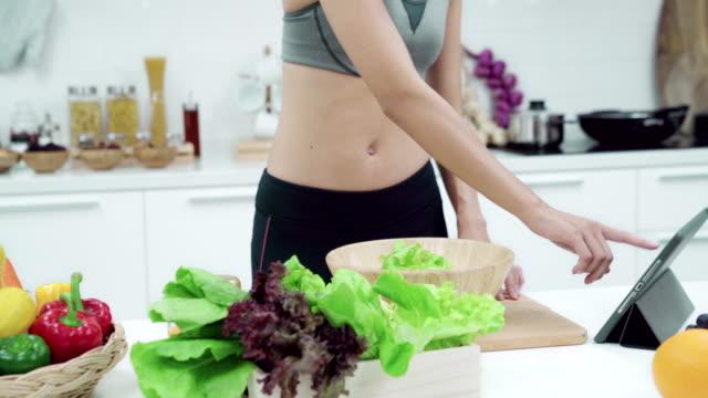 nahe der asiatischen frau der hand sucht rezept für das frühstück nach dem training in der küche zu hause. gesundes essen und gesundes lifestyle-konzept. - abnehmen stock-videos und b-roll-filmmaterial