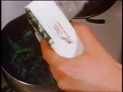 1958 close up hands emptying package of green beans into pot on stove / newsreel - cibi surgelati video stock e b–roll
