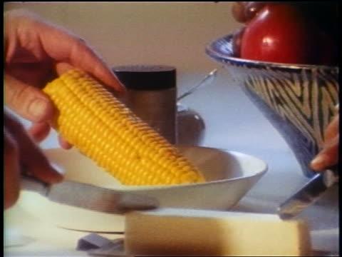 vídeos y material grabado en eventos de stock de 1958 close up hands grabbing corn on the cob + spreading butter with knife / newsreel - mantequera vajilla