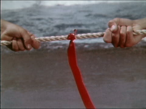 vidéos et rushes de 1961 close up hands holding rope on either side of red ribbon during game of tug of war on beach - corde