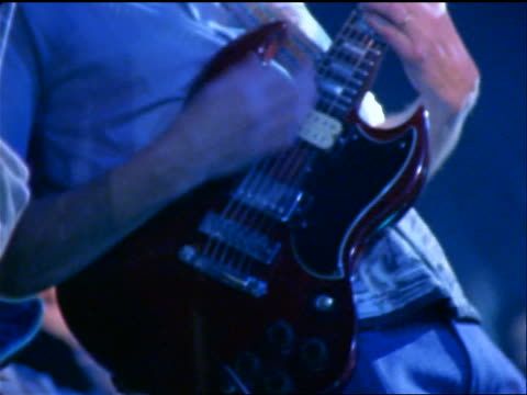 vídeos de stock, filmes e b-roll de blue close up hands of 2 electric guitarists playing in rock concert - performance