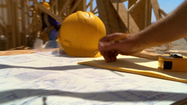 Close up hands of architect writing on construction blue print with house frame and workers in background / Texas