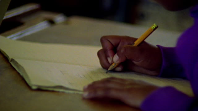 close up hands of black child seated at desk writing with pencil on notepaper / south africa - writer stock videos & royalty-free footage