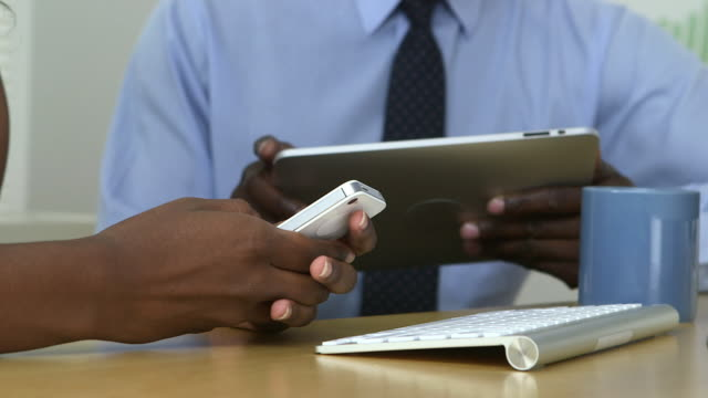 Close up hands of business partners texting and using tablet pc