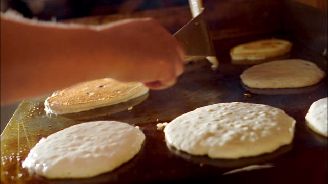 Close up hands of cook flipping rows of pancakes w/spatula on hot griddle