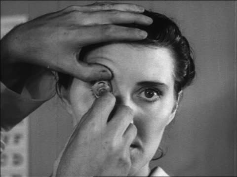 stockvideo's en b-roll-footage met b/w 1936 close up hands of doctor placing contact lens into woman's eye / newsreel - oogmeetkunde