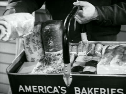 b/w 1938 close up hands of door-to-door salesman picking up jellyroll from basket / industrial - door to door salesperson stock videos & royalty-free footage