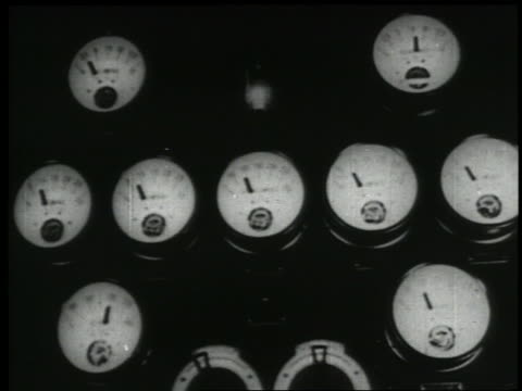 B/W 1938 close up hands of gauges for recording levels moving in control room of radio studio