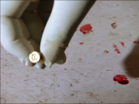 close up hands of investigator picking up bullet off of bloody floor and placing in evidence envelope - kriminaltechnik stock-videos und b-roll-filmmaterial