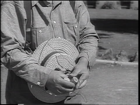 b/w 1937 close up hands of man attaching batteries to wires connected to straw hat - straw hat stock videos & royalty-free footage