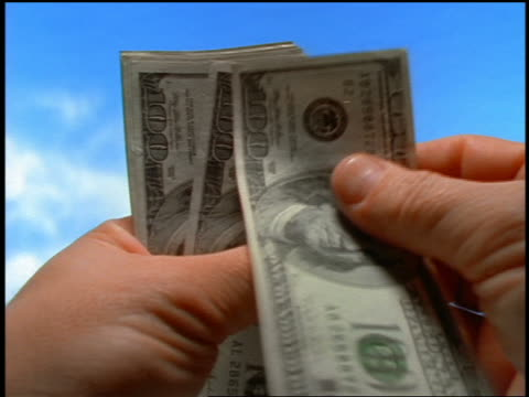 close up hands of man counting 100 dollar bills / blue skies in background