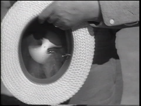 b/w 1937 close up hands of man displaying straw hat with tiny spinning fan + motor for camera - straw hat stock videos & royalty-free footage