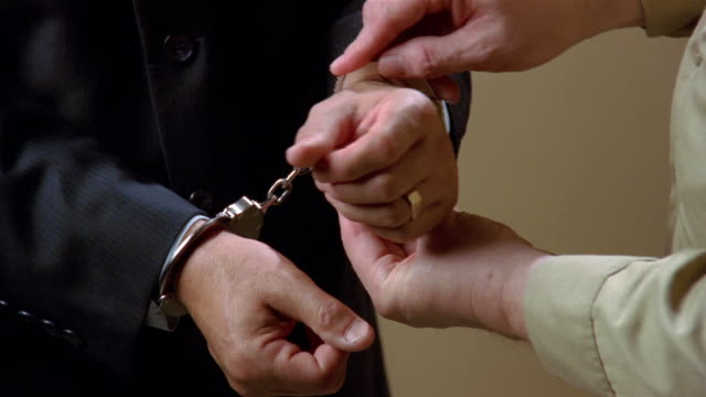 Close up hands of man in suit being handcuffed/ zoom in hands in cuffs