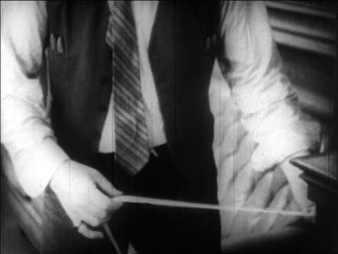 B/W 1929 close up hands of man looking at ticker tape / New York Stock Exchange / newsreel