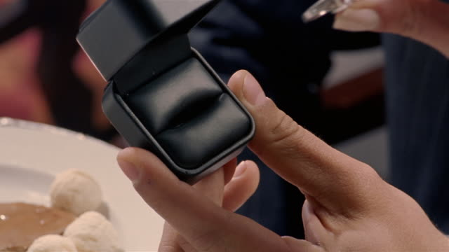 Close up hands of man opening box containing ring/ manicured hands of woman trying on ring/ holding hands