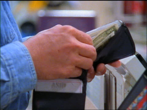 close up hands of man paying cashier in cash at checkout register in supermarket