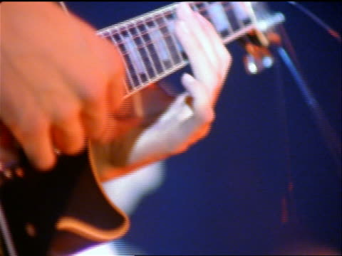 close up hands of man playing electric guitar in rock concert - エレキギター点の映像素材/bロール