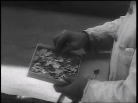b/w 1938 close up hands of man playing with puzzle in box outdoors / newsreel - puzzle video stock e b–roll