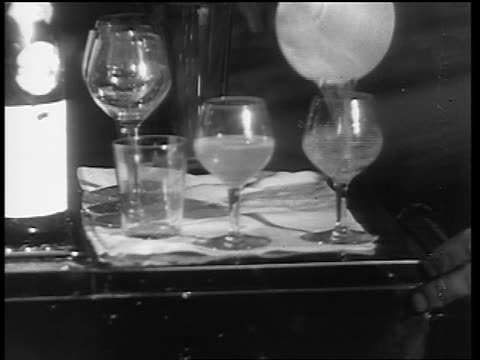 b/w 1933 close up hands of man pouring drinks into glasses from shaker / end of prohibition - 1933年点の映像素材/bロール