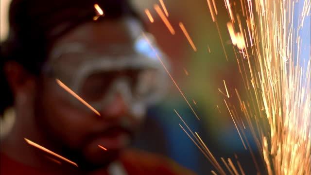 vídeos y material grabado en eventos de stock de close up hands of man sanding metal object w/sparks flying / tilt up face of black artist wearing goggles - sparks