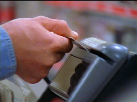 close up hands of man swiping card at checkout register in supermarket + punching in numbers