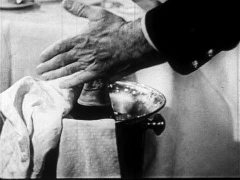 B/W 1928 close up hands of man twisting champagne bottle in ice bucket / newsreel