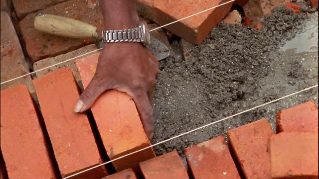 Close up hands of mason laying bricks evenly / Patan, Nepal
