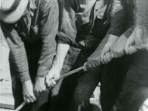 b/w 1934 close up hands of men pulling rope in wpa construction project / documentary - 雇用促進局点の映像素材/bロール