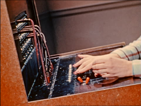 1941 close up hands of operator plugging in wires at switchboard / industrial