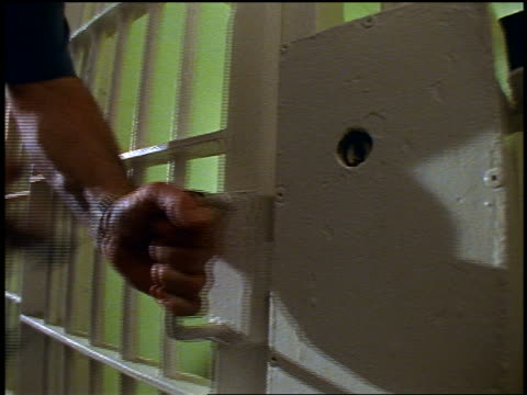 vídeos de stock e filmes b-roll de close up hands of prison guard closing + locking prison cell door with keys - preso