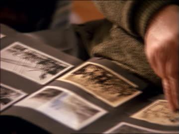 stockvideo's en b-roll-footage met close up hands of senior man + boy looking at b/w photos in album - fotografische thema's
