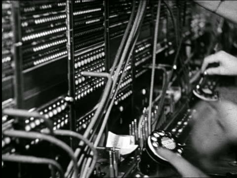 b/w 1946 close up hands of telephone operator plugging in wires at switchboard / industrial - 電話交換機点の映像素材/bロール