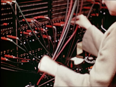 1945 close up hands of telephone operator plugging in wires at switchboard / industrial - 電話交換機点の映像素材/bロール
