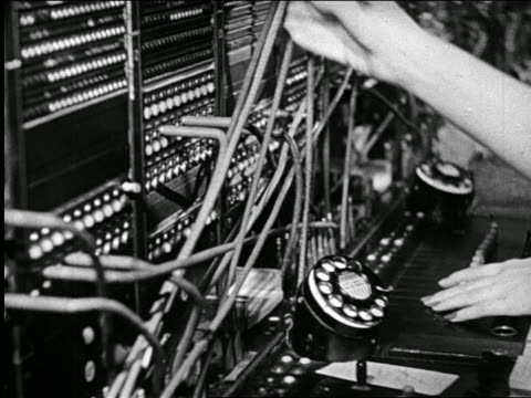 B/W 1946 close up hands of telephone operators plugging in wires at switchboard / industrial