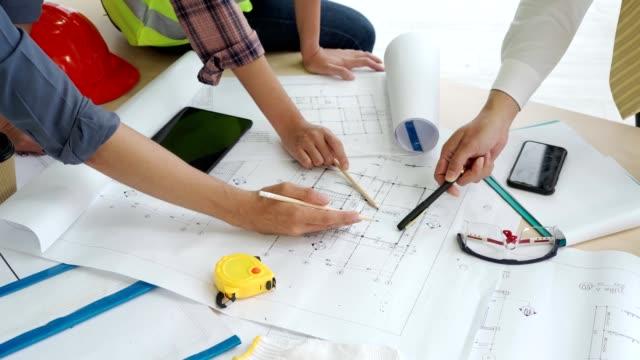 vídeos de stock, filmes e b-roll de feche as mãos de três trabalhadores discutindo desenhos de construção no escritório - compasso