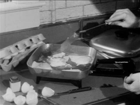 B/W 1957 close up PAN hands of woman frying eggs on electric pan / man grabbing electric percolator
