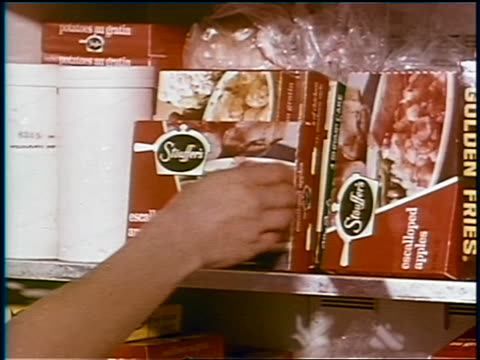 1969 close up hands of woman grabbing box of Stouffer's frozen escalloped apples / industrial