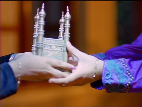 close up pan hands of woman handing model of charminar to smiling indian girl / mumbai, india - 1999 stock videos & royalty-free footage