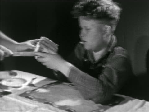 vídeos de stock e filmes b-roll de b/w 1938 close up pan hands of woman handing slice of cake to plump boy who eats it / educational - overweight