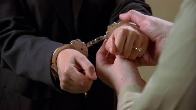 vídeos de stock, filmes e b-roll de close up hands of woman in suit being handcuffed/ zoom in hands in cuffs - algema