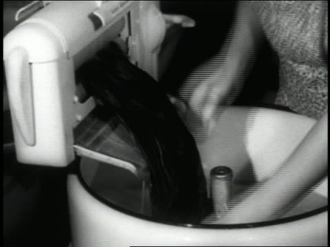 b/w 1940 close up hands of woman loading wet clothes from early washing machine through wringer - washing stock videos & royalty-free footage