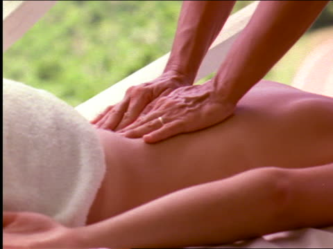vidéos et rushes de close up hands of woman massaging back of second woman with towel over buttocks - se faire dorloter