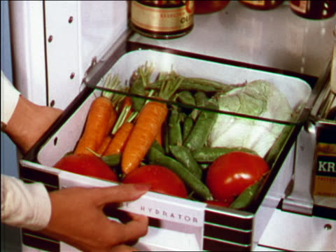 1949 close up hands of woman opening crisper drawer of fridge filled with vegetables / industrial - drawer stock videos and b-roll footage