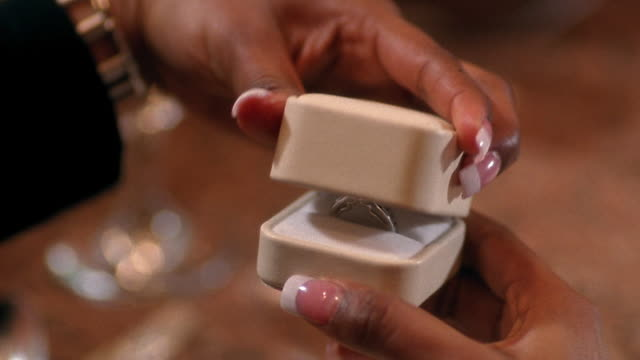 Close up hands of woman opening jewel box with diamond ring inside