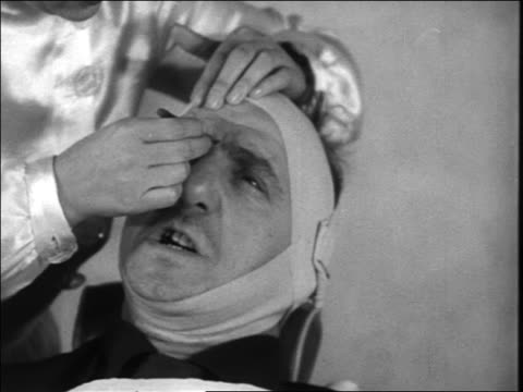 B/W 1938 close up hands of woman plucking eyebrows of Jimmy Durante in chair in beauty parlor / newsreel