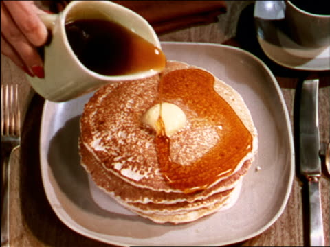 1949 close up hands of woman pouring syrup on pancakes / industrial - pancake stock videos & royalty-free footage