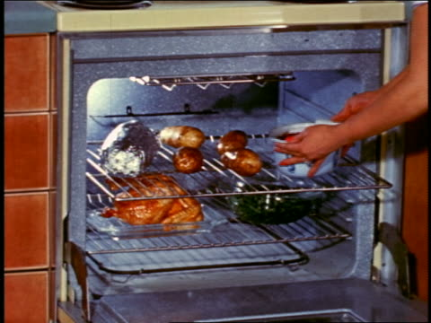 1958 close up hands of woman putting pot with food into oven filled with cooking food