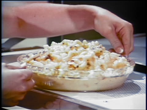1969 close up hands of woman removing macaroni and cheese casserole from oven / industrial