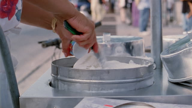 Close up hands of woman serving ice cream / young man taking ice cream and walking away
