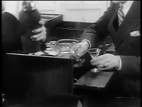 B/W 1936 close up hands of woman shaking cocktails as man takes glasses from desk / liquor cabinet
